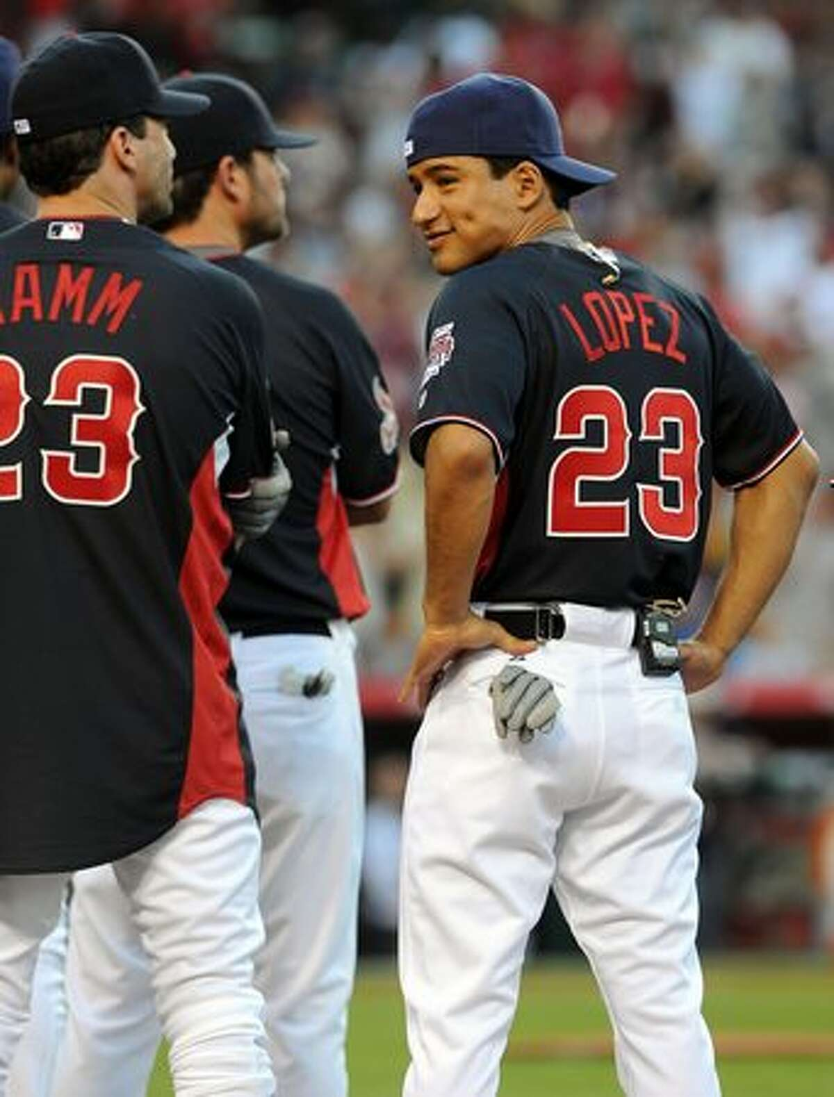 TV personality Mario Lopez (R) looks back at actor Jon Hamm (L) during the MLB All Star Game Celebrity Softball Game at Angels Stadium in Anaheim, California.