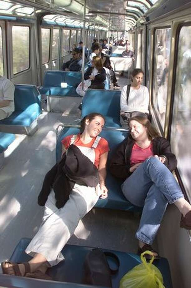 Amy Jo Diebold and Jenny Stewart relax during their daily commute from downtown on the monorail, June 19, 2000. Photo: P-I File