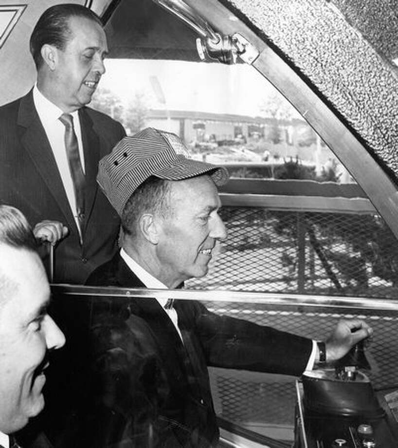Walter Straley, president of the Century 21 Center, Inc. at the controls of the Monorail blue train, and Sixten Holmquist of Alweg, the Monorail builder. [Exact date unknown.] Photo: P-I File