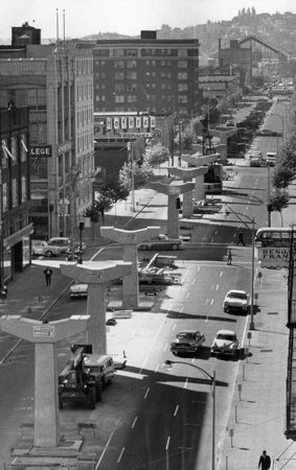 The June 1961 photo caption read: T-shaped pylons for Seattle's new monorail to serve Century 21 Expostition are erected in middle of Fifth Avenue. Photo: P-I File