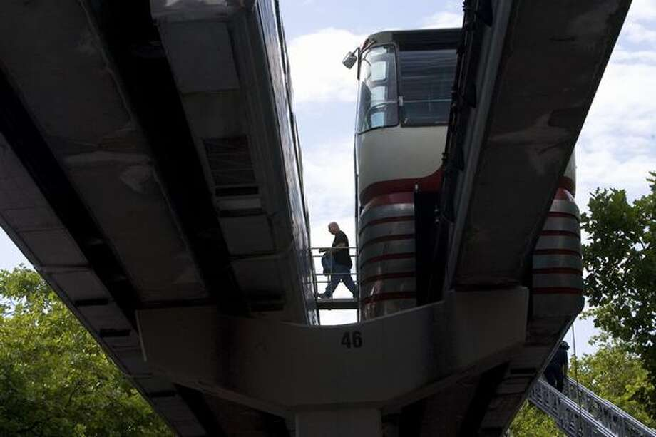 A passenger travels from the red Monorail car, right, to the blue car after the red car developed electrical problems in August 2008. (Grant M. Haller/Seattlepi.com file) Photo: P-I File
