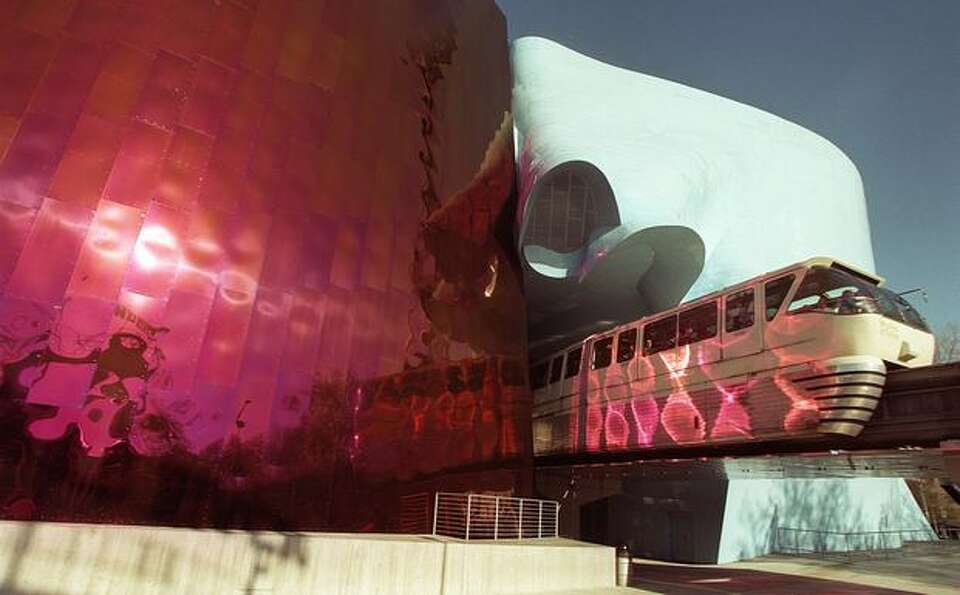 The Monorail, reflected in the Experience Music Project, moves along its track near the Space Needle