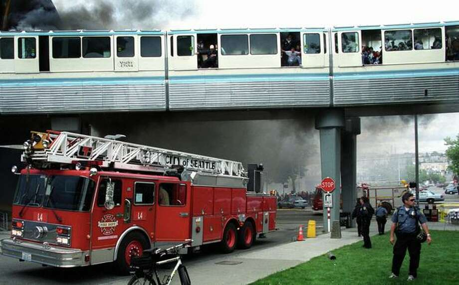 The May 2004 caption read: Passengers on the Seattle Monorail crowd in one side of the Seattle icon as smoke envelopes the train near the intersection of Fifth Avenue and Broad Street. The train caught fire after passing through the EMP tunnel en route to the Westlake Center. There were no serious injuries in the incident. Photo: P-I File