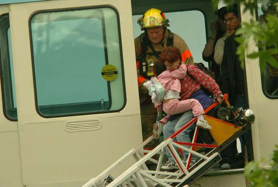 The May 2004 caption read: A woman with her child are helped out of the blue Monorail car by Seattle firefighters as the fire was being extinguished in another part of the car. Photo: P-I File