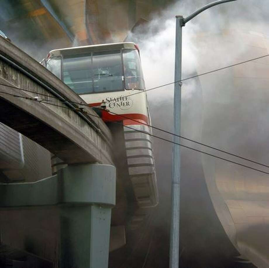 The May 2004 caption read: Smoke from the blue Monorail car blows over the red car near the Seattle Center in downtown Seattle Washington. Photo: P-I File