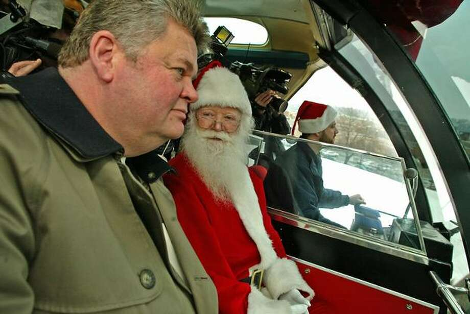 Santa and Seattle Mayor Greg Nickels chat during a December 2004 ride on the Seattle Monorail. Photo: P-I File