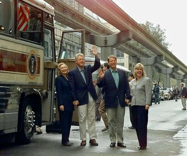 The Sept. 19, 1996 photo caption read: President Clinton waves as he boards a bus with First Lady Hi