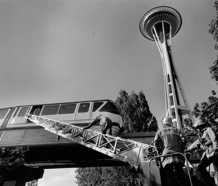 Firefighters check a Monorail train after it blew a tire near the Seattle Center, September 1984. A
