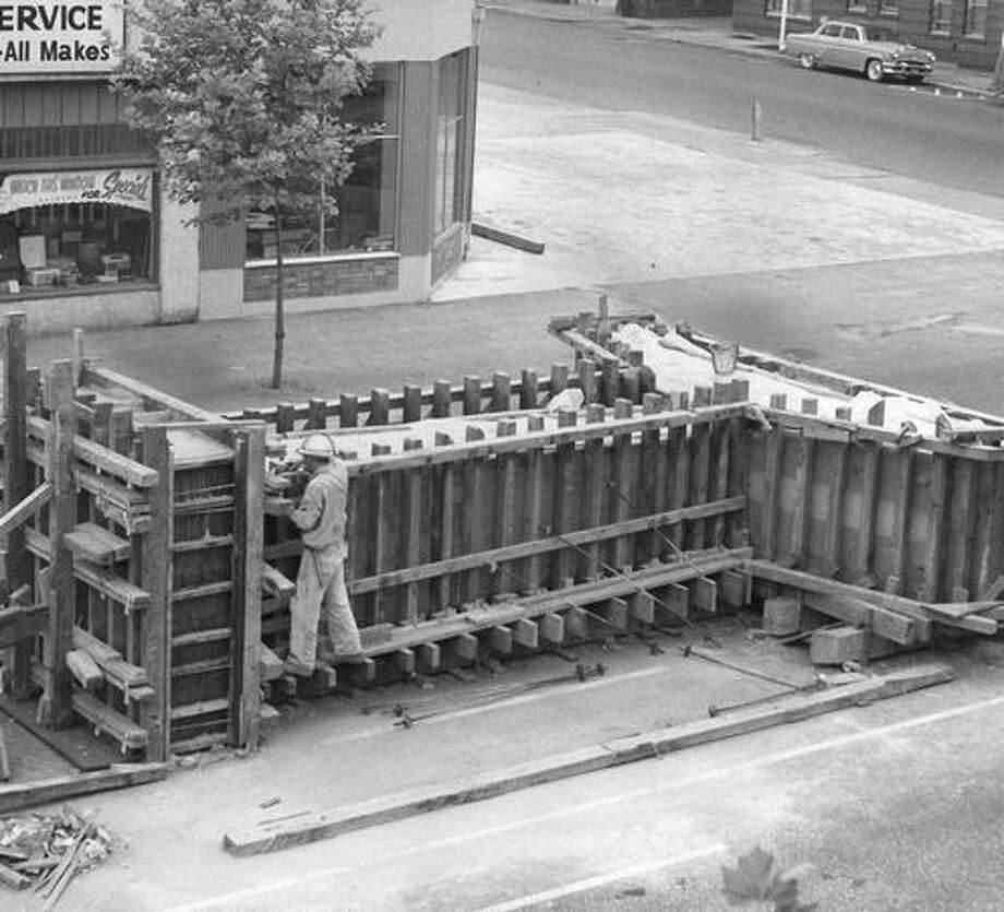 The June 1961 caption to this Westlake station photo read: Heavey braced forms hold 22.5 yards of concrete poured into the steel cage to cast colum from T-section to anchoring pad. Photo: P-I File