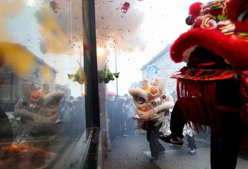 Members of the Mak Fai Washington Kung Fu Club perform a lion dance in front of a business during the Year of the Rabbit Lunar New Year celebration in Seattle's International District on Saturday, Jan. 29, 2011. Crowds braved the rain to participate in the annual event in Seattle.