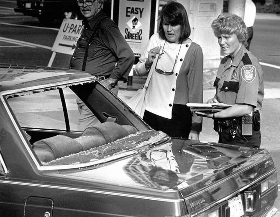 Nancy Richardson, next to a Seattle Police officer, looks at her broken rear windshield. It shattered when a Monorail from above popped a windshield that came crashing down onto Fifth Avenue, Aug. 27, 1987. Photo: P-I File