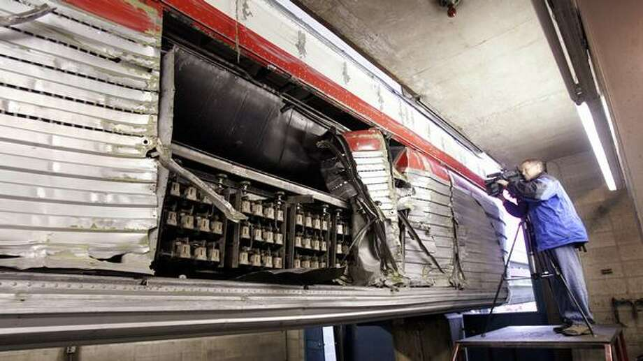 A television photographer records damaged lower panels of monorail train during a media tour of the train at the Seattle Center maintenance shop, Dec. 5, 2005. Photo: P-I File