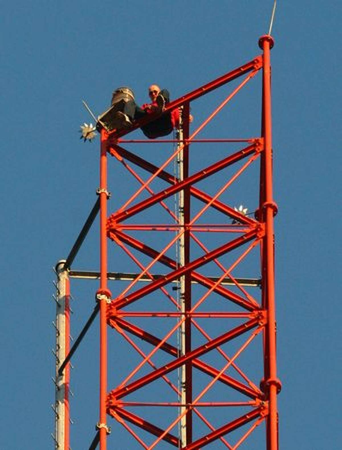 A man sits on the top of the 609-foot KIRO/7 Television tower on Seattle's Queen Anne hill. Hundreds of onlookers gathered to watch as the man climbed to the top of the tower, sat on the top for about 15 minutes, and then climbed back down. He was detained by police after reaching the ground.