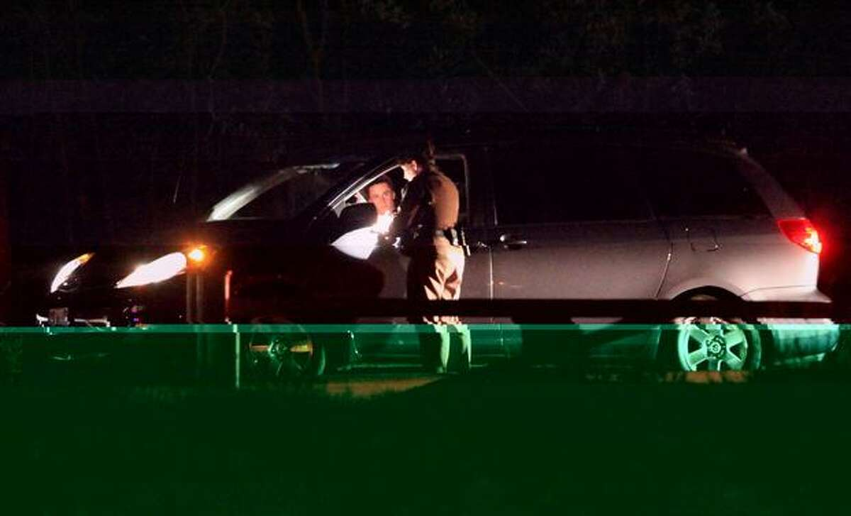 Police interview and inspect cars leaving Lake Sammamish State Park after a shooting left at least two dead and four others wounded Saturday night. The park was placed in lockdown afterward and park-goers were not allowed to leave without being questioned and cleared by police.