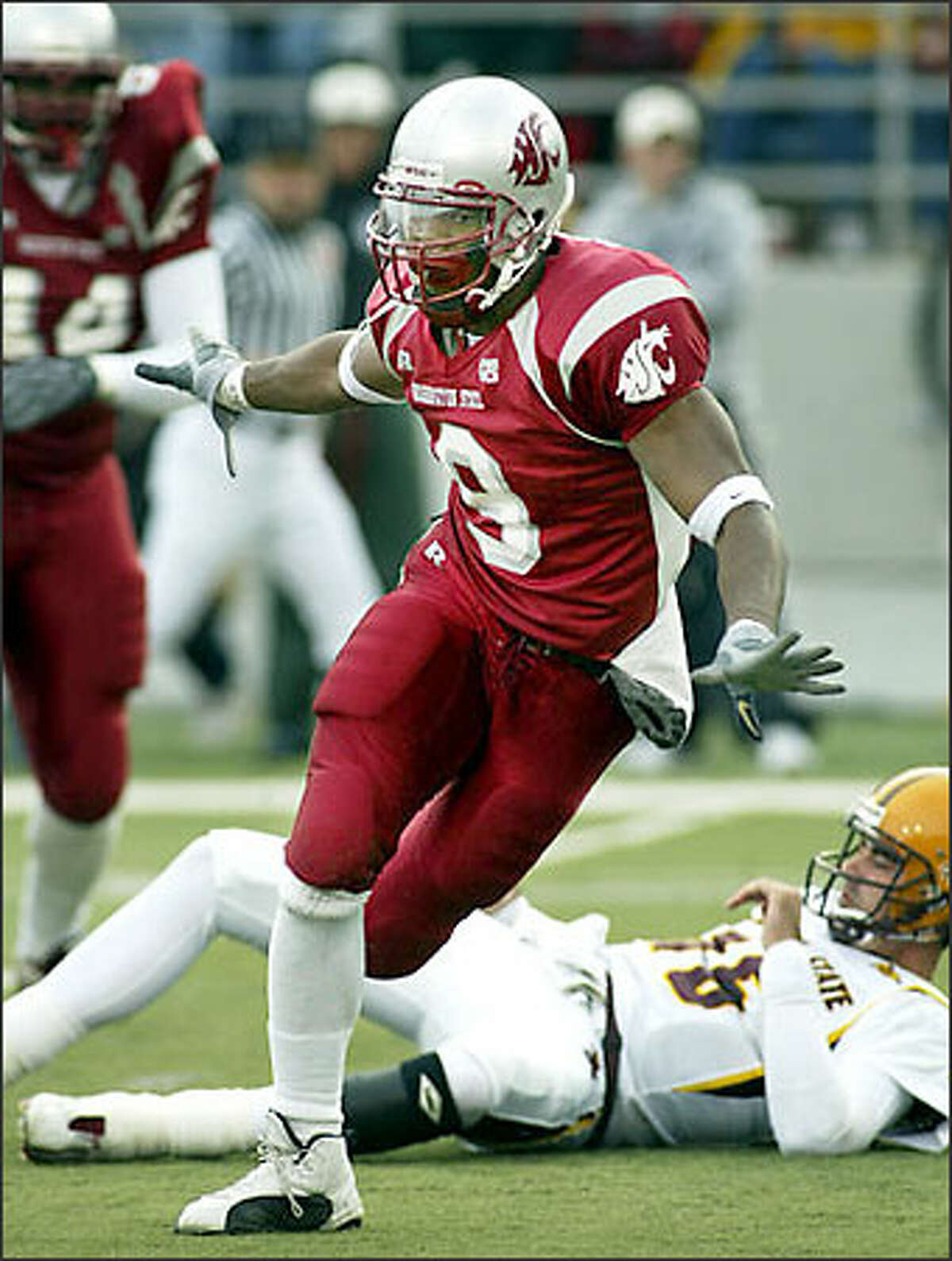 Washington State defensive end Isaac Brown celebrates after he sacked Arizona State quarterback Andrew Walter, who lies on the field behind Brown in the first quarter Saturday, Nov. 15, 2003, at Martin Stadium in Pullman. (AP Photo/Ted S. Warren)