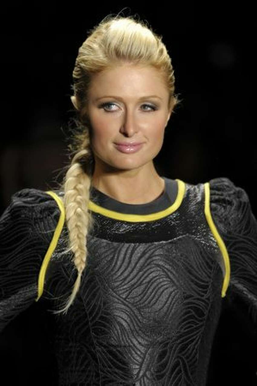 Socialite Paris Hilton presents a creation by Triton during the opening day of the 2011-2012 Fall-Winter collections of the Sao Paulo Fashion Week in Sao Paulo, Brazil.