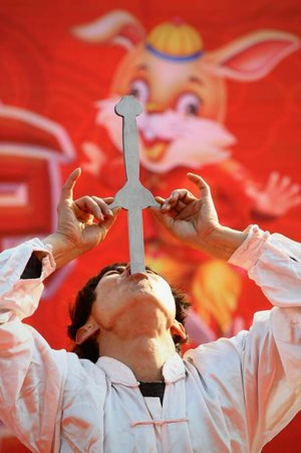 A Chinese folk artist puts the double-edged sword into mouth at a temple fair to celebrate the Lunar New Year of Rabbit in Beijing, China. Photo: Getty Images