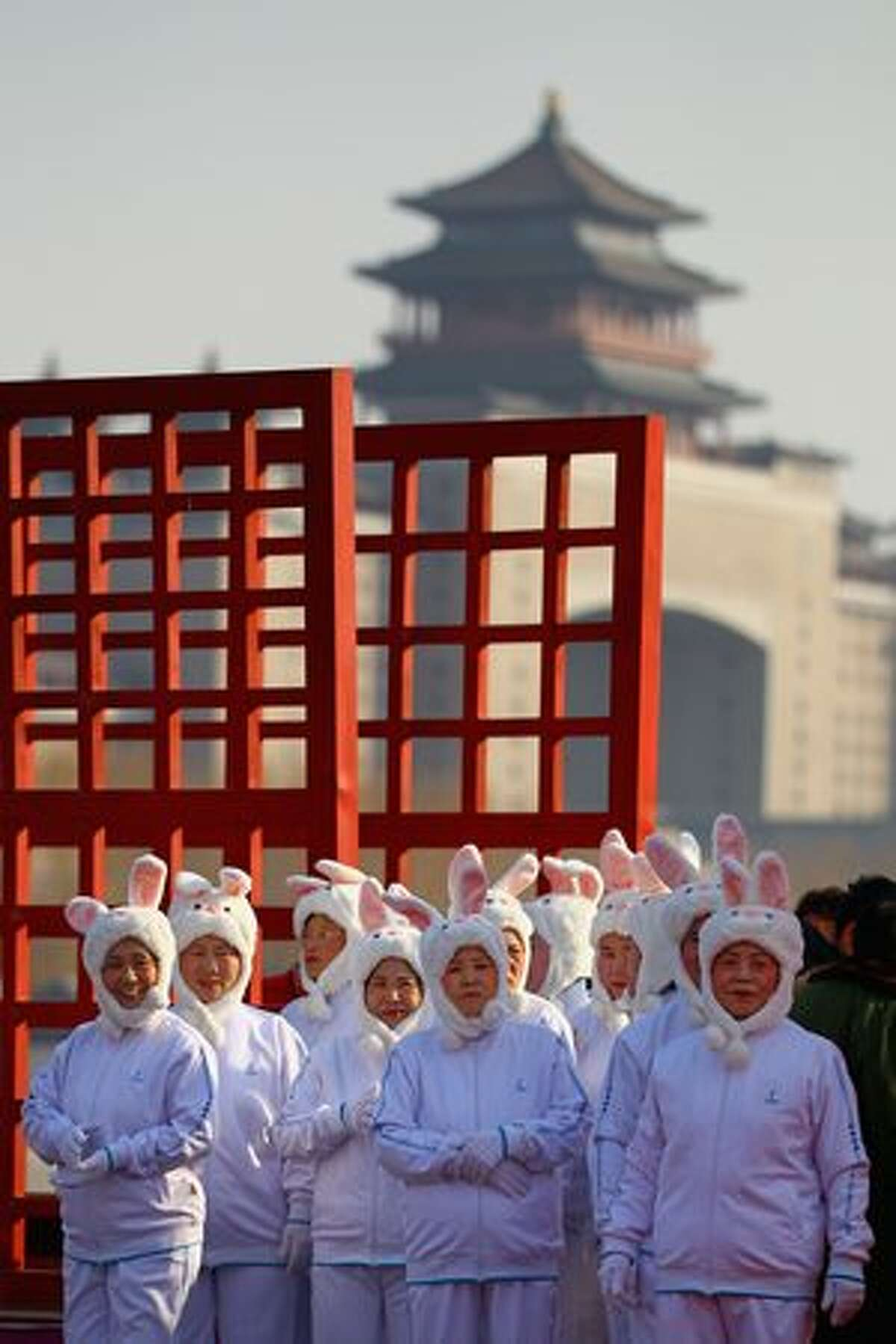 Chinese folk artists dressed in rabbit costume prepare to perform at a temple fair to celebrate the Lunar New Year of Rabbit in Beijing, China.