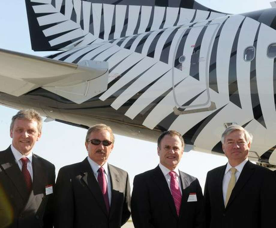 (From right) Airbus Chief Operating Officer John Leahy, Air New Zealand Financial Chief Executive Officer Rob McDonald, Air Lease Corporation President Stevan Udvar-Hazy and International Aero Engines President Ian Aitken pose in front of an A320 Airbus delivered to Air New Zealand and painted with the logo of New Zealand rugby national team, the All Blacks. Photo: Getty Images