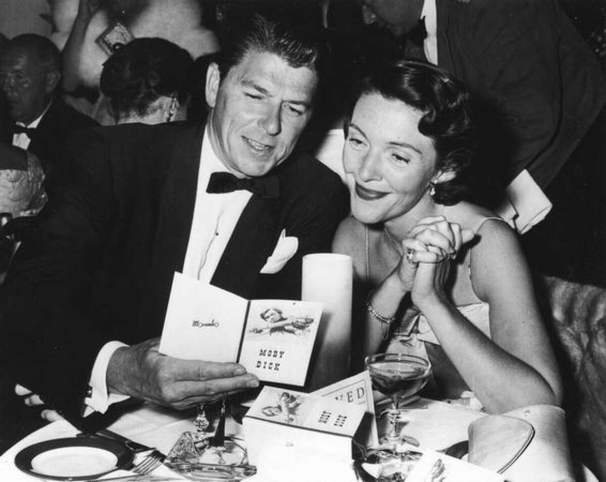 American actor Ronald Reagan and his wife, Nancy Reagan sit at a restaurant table, looking at a brochure at the premiere party for the film, 'Moby Dick,' directed by John Huston in,1956.