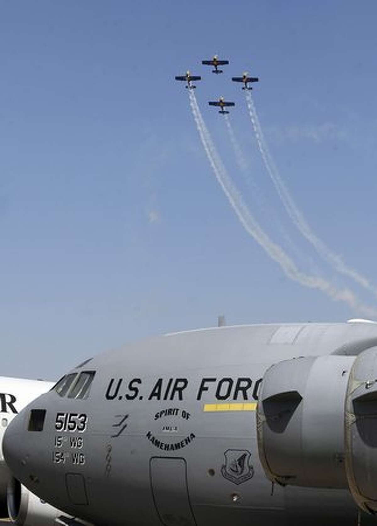 The Red Bull aerobatics team flies in formation past a U.S. cargo aircraft on the eve of the Aero India 2011 exposition at the Yelhanka Air Force station in Bangalore.
