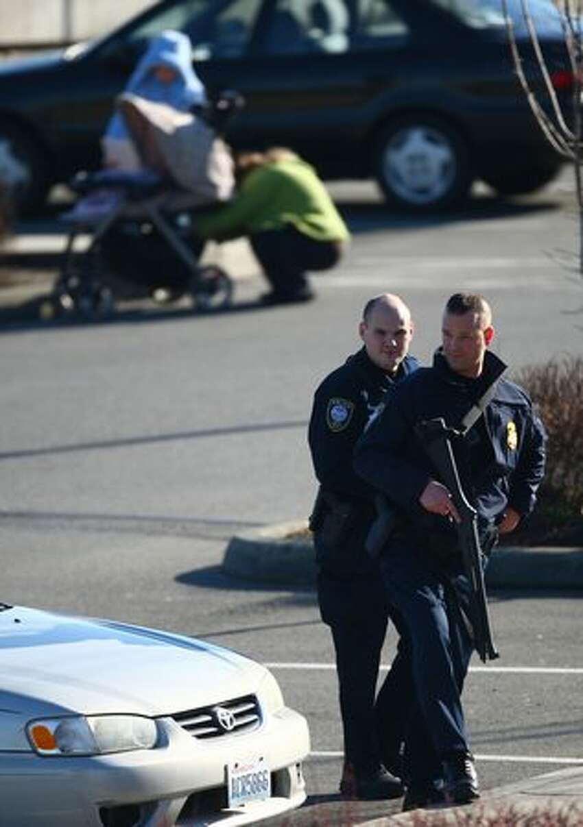 Federal Protective Service officers from the Department of Homeland Security help search Thursday for a suspect who escaped during a burglary investigation. Tukwila police shot another suspect after he reportedly hit an officer with a car. Police warned residents to stay indoors as they continued searching for the second suspect. Photographed on Thursday, February 10, 2011.