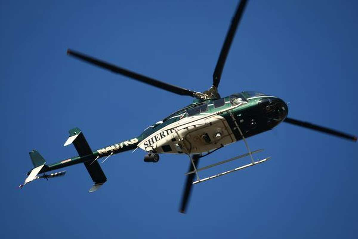 King County Sheriff's Office helicopter, Guardian One, helps search for a suspect who escaped during a burglary investigation. Tukwila police shot another suspect after he reportedly hit an officer with a car. Police warned residents to stay indoors as they continued searching for the second suspect. Photographed on Thursday, February 10, 2011.