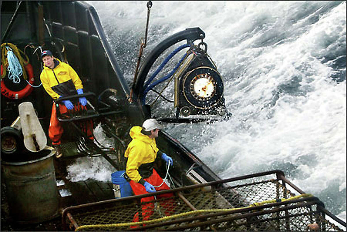 """F/V Exito crewmen Lee Fleury prepares to throw the grappling hook at a crab pot buoy off in the distance while Lyndon Yockey, rear, runs the hydraulics to manuever heavy crab pots to be stacked onboard.Ducey: """"The 2003 Bristol Bay red king crab season lasted five days and was plagued by gale-force winds of 35 knots or more almost every day, causing to seas to rise 10 to 15 feet. I was seasick the whole time."""""""
