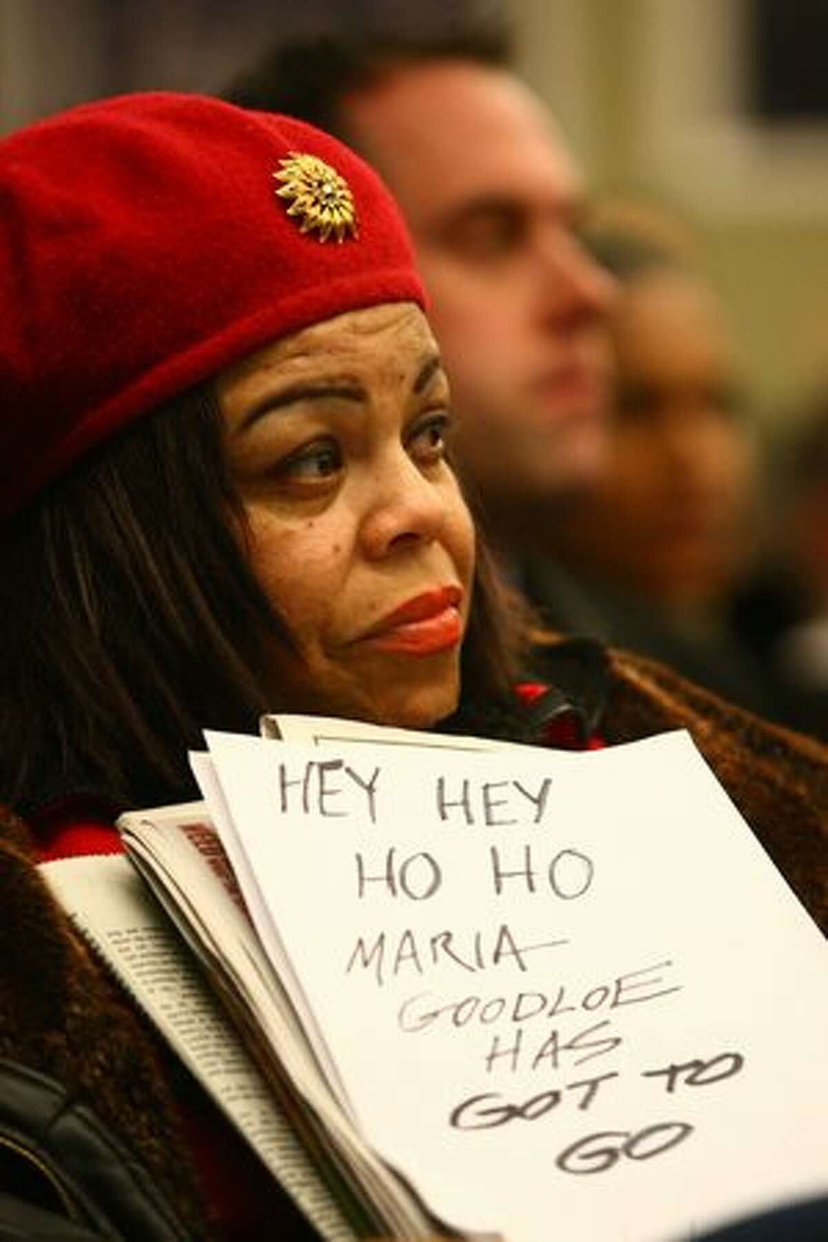 Marguerite Richard holds a sign during a meeting of the Seattle Public School Board of Directors.
