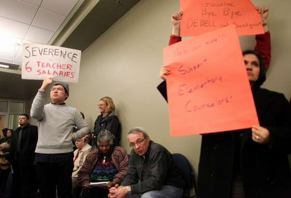 People hold signs during a meeting of the Seattle Public School Board of Directors at the John Stanford Center for Educational Excellence in Seattle on Wednesday, March 2, 2011. The directors voted to terminate the contract of Superintendent Maria Goodloe-Johnson after a contracting scandal engulfed the district.