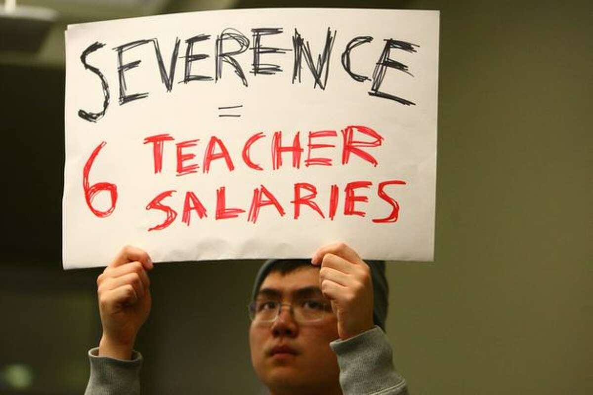 Johnny Mao holds a sign during a meeting of the Seattle Public School Board of Directors.
