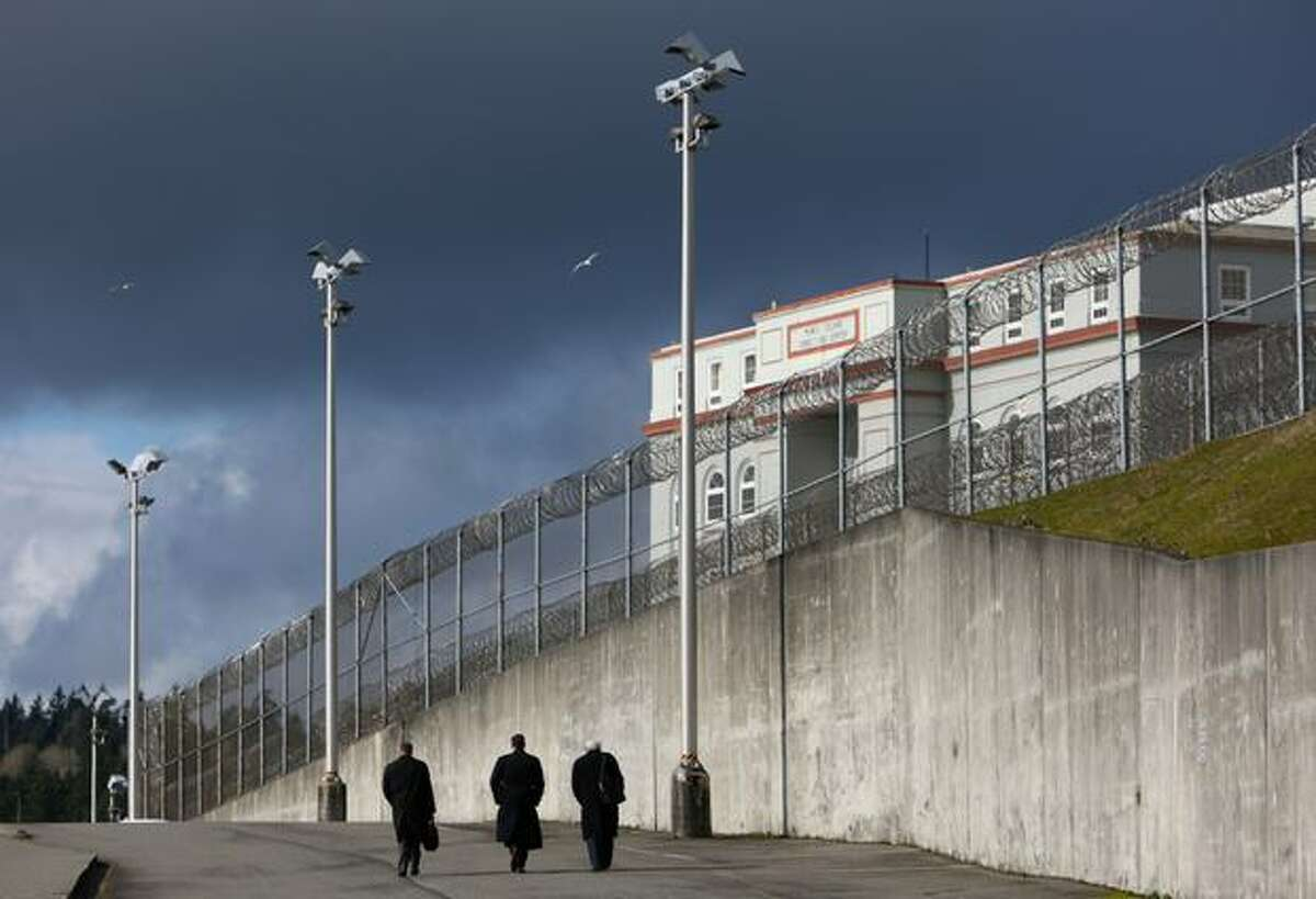 Dignitaries, including Department of Corrections Secretary Eldon Vail, walk to the prison during the closing ceremony for McNeil Island Corrections Center on Thursday, March 3, 2011. McNeil Island has been housing inmates since 1875 and in 1904 became a federal prison. It later became part of the Washington State prison system. It will be closed due to budget cuts. The remaining inmates will be distributed to other Washington facilities.