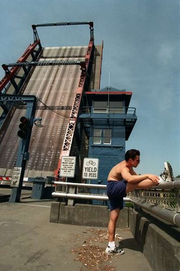 The May 1998 photo caption read: Christopher Togawa of Seattle stretches after his afternoon run was interrupted by the opening of the Fremont Bridge. Photo: P-I File