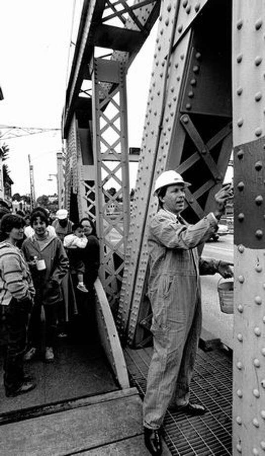"The June 1984 caption read: Mayor Charles Royer puts a test swatch of ""pickle green"" on a strut of the Fremont Bridge. Other officials yesterday painted patches of four other colors that are candidates to replace the faded orange the bridge was decked out in during the '70s. Photo: P-I File"