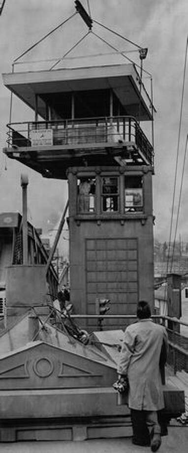 The Feb. 9, 1960 caption read: A new deck is lowered by crane onto the control tower of the Fremont Bridge yesterday. The deck, which gives the tower a second story, is one of a series of improvement to bring the span up-to-date. All new electrical control equipment is being installed. Old roof of tower can be seen on sidewalk. Photo: P-I File