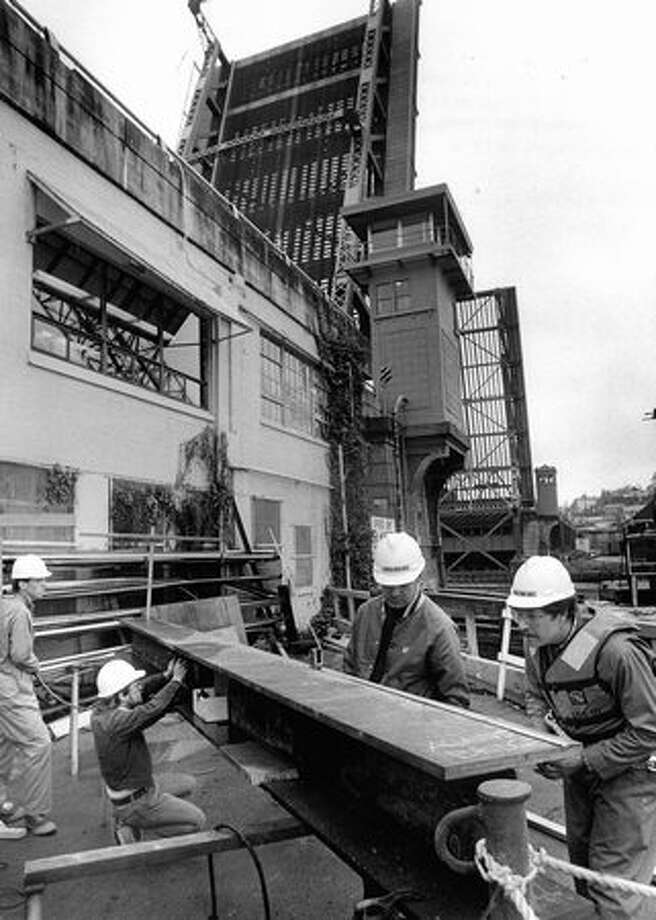 The October 1986 caption read: Timothy Lane, Mike Dague, Rich Miller, and Roy Ruden construct a temporary beam that will be welded under damaged structure on Fremont Bridge. The bridge will then be lowered and damaged area will be removed. Photo: P-I File
