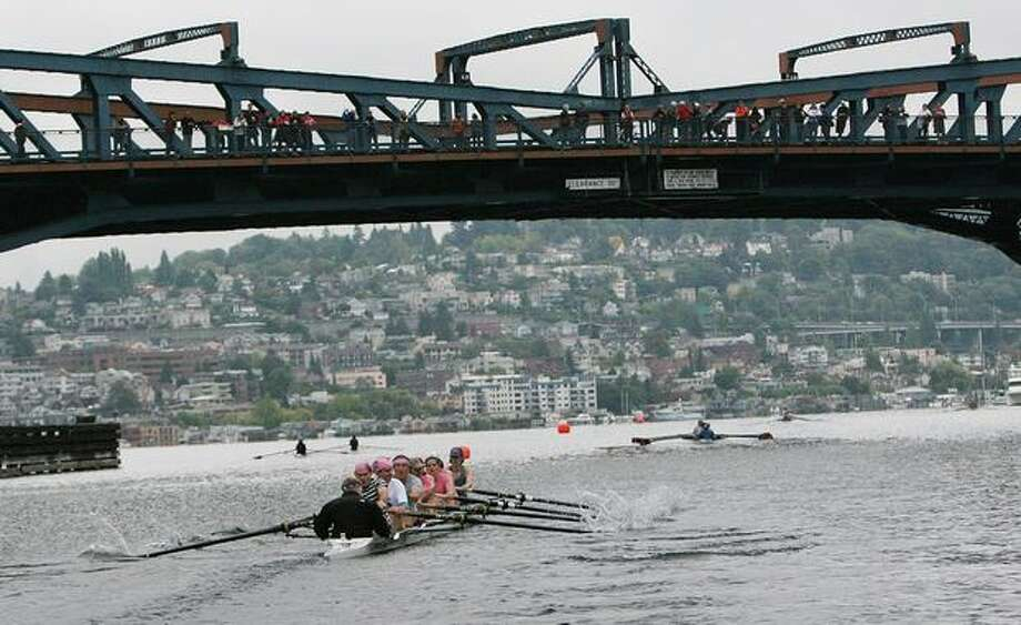 Fans watch from the Fremont bridge as one of the first boats pushes toward Lake Union during the 4.5 kilometer race fundraiser event by the Row for the Cure regatta on Sept. 21, 2008. Photo: P-I File