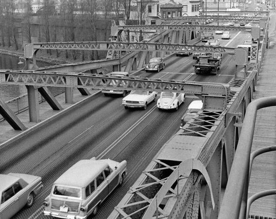 The June 1984 caption read: Normal daytime traffic crossing the Fremont Bridge. The Bridge tender waits for a hole in the traffic before operating signals to stop cars so bridge can be opened. Photo: P-I File