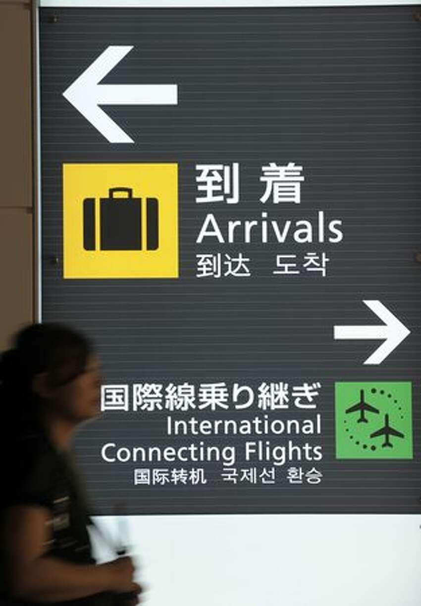 A woman walks in front of signage inside the new international terminal building at Tokyo International Airport. The terminal is scheduled to open on Oct. 21 this year.