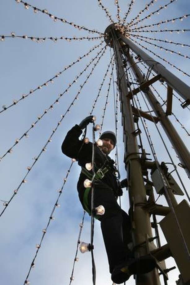 Benjamin Marshall, an engineer for the Space Needle, changes Christmas lights in December 2007. Photo: P-I File