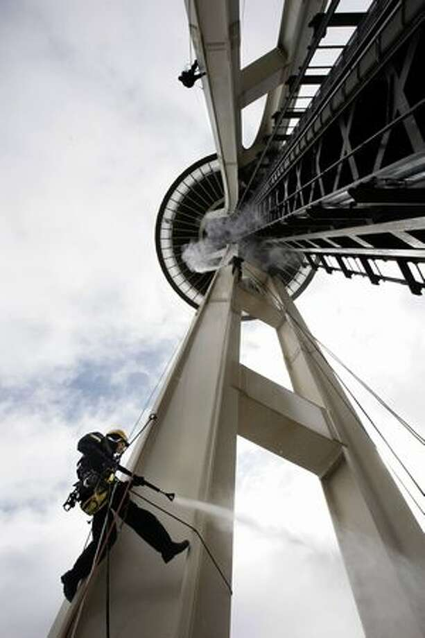 Matt Henry, bottom, Matthew Waskiewicz, center and Nathan Schuster, top, rope access technicians with Skala, demonstrate how they use heated, high-pressure water to clean the surface of the Space Needle, May 2008. Photo: P-I File