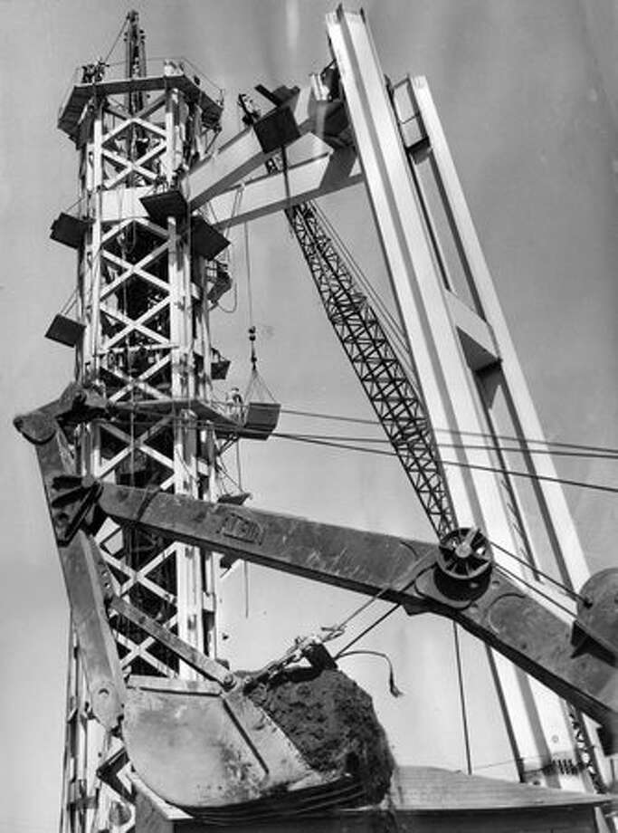 The 1961 photo caption read: The first two of six supporting columns for the World's Fair Space Needle are shown being connected to the needle's center core, 100 feet from the base. The 50-ton legs are 90 feet long and are connected to the core by 30-foot crossbars. The Spce Needle will rise 600 feet and will feature a revolving restaurant at the top. Photo: P-I File