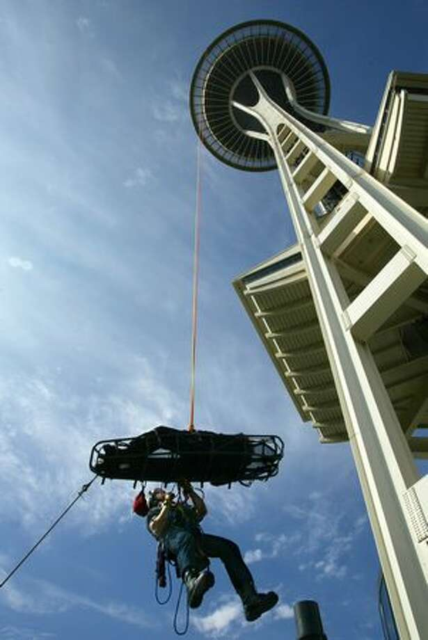Jessie Domski, of the Seattle Fire Department technical rescue team, practiced rescuing a mock patient and rappels down the Space Needle with a stretcher in July 2004. Photo: P-I File