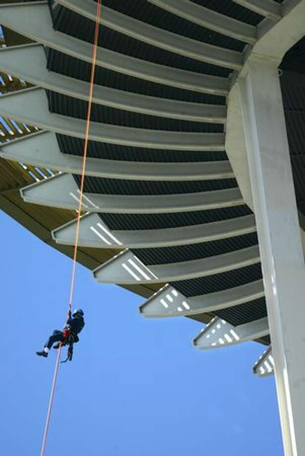 Eric Baker, of the Everett Fire Department, repels over the side of the Space Needle during a training exercise, July 2004. Photo: P-I File