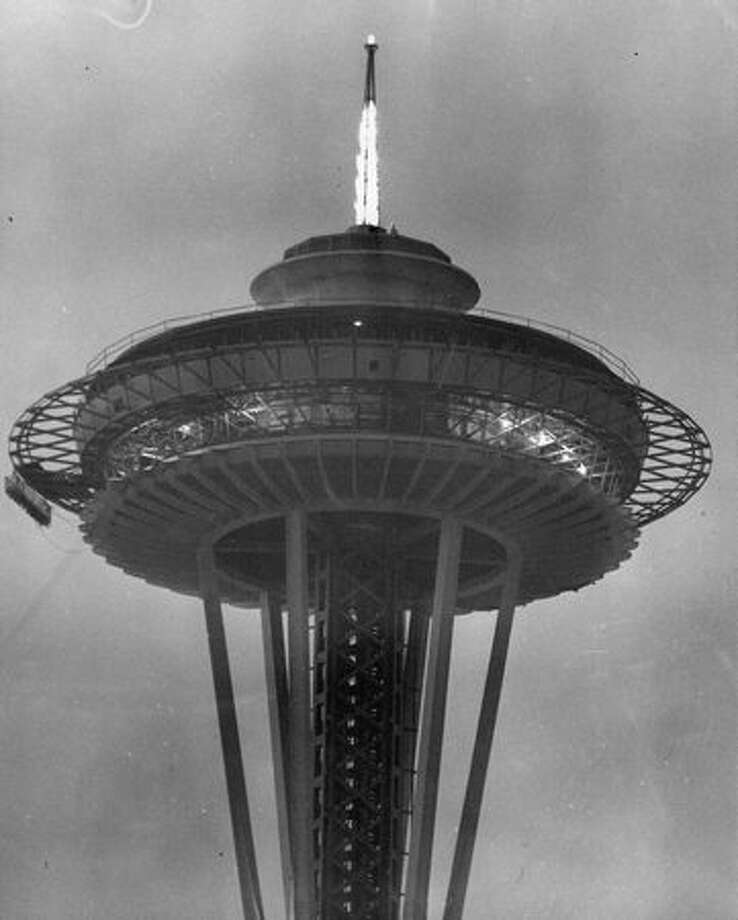 The Space Needle, early 1962. Note the flames coming from the antenna; the Needle was equipped with natural gas, which was burned at the top periodically for dramatic effect. Photo: P-I File