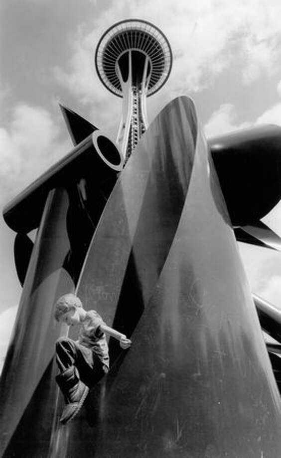 The June 1993 photo caption read: As renovation continues high and low at the 31-year-old Seattle Center, Evan Summers, 7, climbs on a sculpture at the foot of the Space Needle. Photo: P-I File