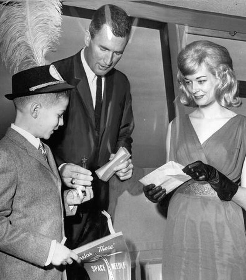 The March 1963 photo caption read: The 3 millionth visitor to the year-old Space Needle, George Adams, 11, receives gifts from Hoge Sullivan, center, as Needle Birthday Queen, Donna Edgin, looks on. (Phil H. Webber/Seattlepi.com file) Photo: P-I File