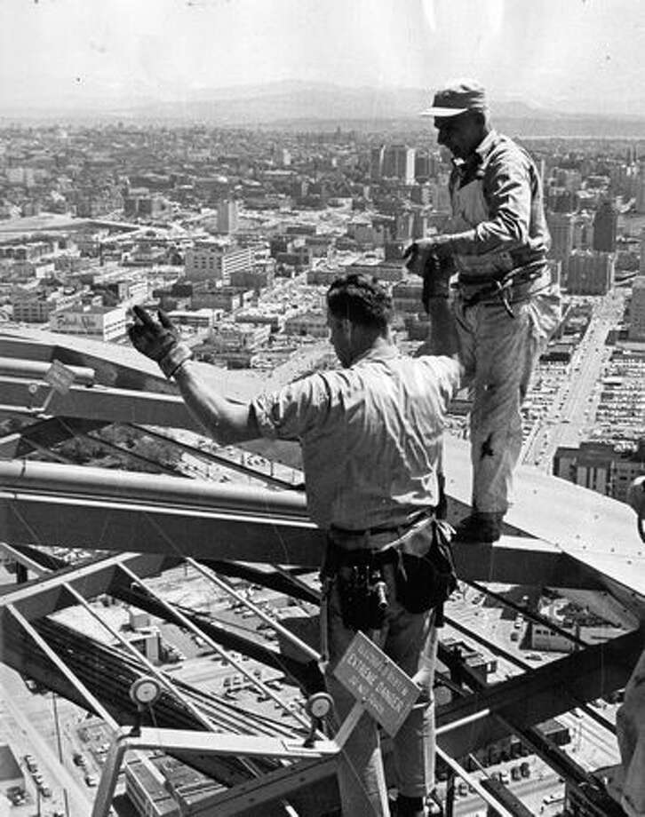 The May 1964 photo caption read: Ken Hazelton, president of Scaffolds & Equipment Inc., helps a painter back toward observation deck of Space Needle during scaffold rigging operation. Photo: P-I File
