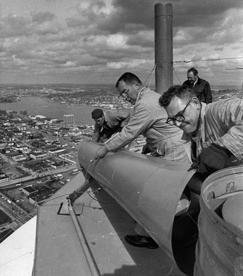 "Workers placed 10th-birthday ""candles"" on the Space Needle, April 1972. Photo: P-I File"
