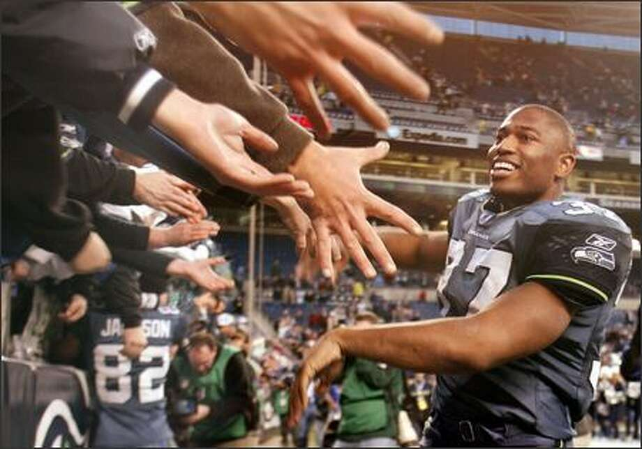 Shaun Alexander slaps hands with the fans after the Seahawks' final home game, where they beat the  against the Cardinals 28-10. Photo: Mike Urban, Seattle Post-Intelligencer